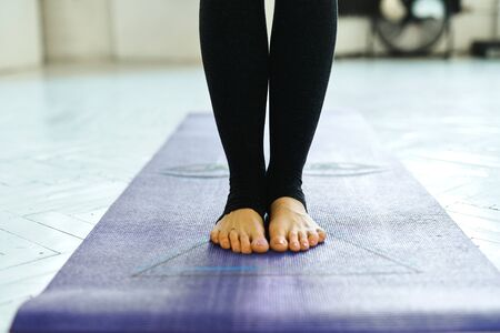 Close-up of woman standing on violet yoga or fitness mat indoor. Yoga Practice Exercise Class Concept. Reklamní fotografie