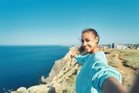 young female tourist making selfie and smile to the camera on cliff edge with beautiful sea view and enjoying wonderful nature. Caucasian female tourist having a great time on her vacation. Zdjęcie Seryjne