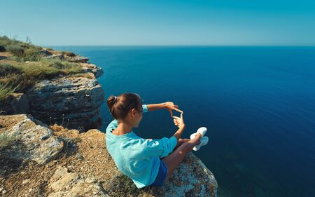 Rear view of young female tourist sitting on cliff edge with beautiful sea view and shows a frame from hands like photo. Photo Frame Hands. Caucasian female tourist having a great time on her vacation.