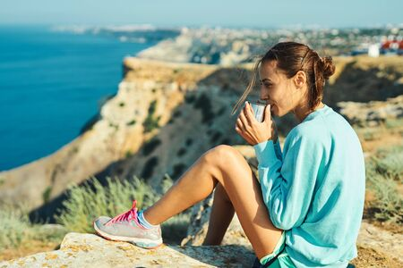 carefree young woman sitting on cliff edge, drinking coffee or tea, enjoying amazing nature view of headland and bay of sea. Caucasian female tourist having a great time on her vacation. Zdjęcie Seryjne