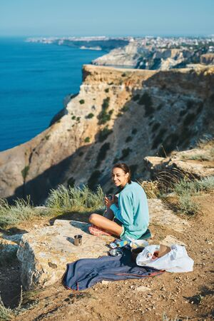 Full length portrait of carefree smiling woman sitting on cliff edge, having a breakfast outdoor on mountain peak with beautiful sea view. Caucasian female tourist having a great time on her vacation.
