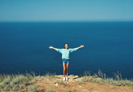 Full length portrait of carefree smiling woman standing with arms spread open on cliff edge with beautiful sea view and enjoying wonderful nature. Caucasian female tourist having a great time on her vacation.