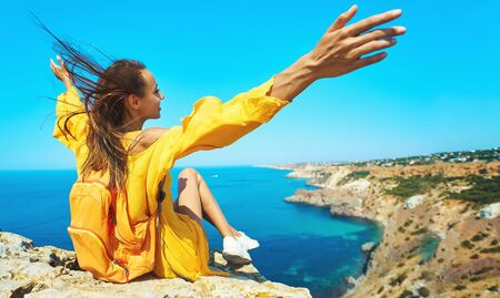 Close up portrait of taned traveler woman sitting on top rock beachwith raised hands in front of amazing seascape, bright yellow dress and hair blowing in the wind. Freedom, travel and vacation concept.