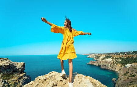 Rear view of taned traveler woman standing on top rock beach with open arms in front of amazing seascape, bright yellow dress and hair blowing in the wind. Freedom, travel and vacation concept.