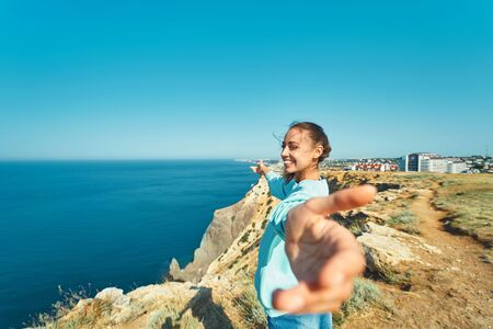 Portrait of happy young standing on cliff edge with beautiful sea view, carefree freedom with open arms in beautiful scenery of natural environment. Follow me, travel, vacation concept.
