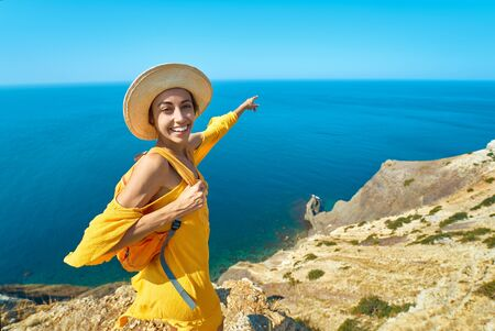 Bright portrait of happy smiling woman in bright yellow dress and hat with backpack standing on cliff edge against amazing seascape, shows towards the sea. Traveler enjoying recreation time and travel.