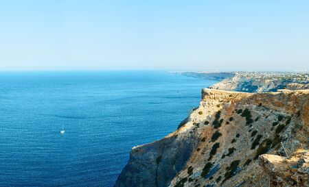 amazing panorama of seashore landscape with high limestone cliff over blue sea and clear deep blue sky. beautiful scenery of natural environment, seascape at summer sunrise Zdjęcie Seryjne