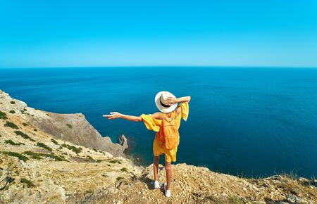 Back view of woman traveler in bright yellow dress and hat with backpack standing the top of mountain with raised hands against amazing seascape, admiring beautiful scenery of natural environment