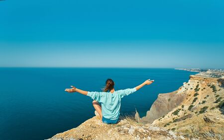 back view of traveler woman sitting on cliff edge with raised hands against beautiful sea view and enjoying wonderful nature. Freedom, travel and vacation concept.