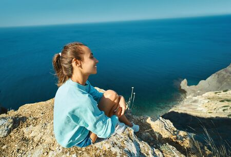 side view of traveler woman sitting on cliff edge with beautiful sea view and enjoying wonderful nature. Freedom, travel and vacation concept.