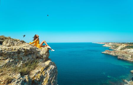 side view of traveler woman in bright yellow dress sitting on cliff edge with beautiful sea view and enjoying wonderful nature. amazing panorama of seashore landscape. Freedom, travel and vacation concept.