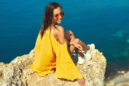 Bright portrait of happy woman in bright yellow dress and red sunglasses smiling to the camera, sitting on cliff edge against amazing seascape. Traveler enjoying recreation time and travel. Zdjęcie Seryjne