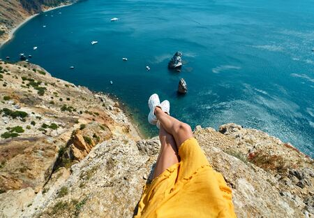 first person view of taned woman legs in yellow dress sitting on on cliff edge with amazing nature view of seascape with high limestone cliff over blue sea and clear deep blue sky. Traveler enjoying recreation time and travel