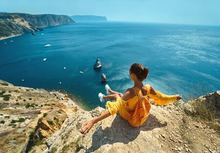 Rear view of female traveler in bright yellow dress with backpack sitting on cliff edge with open arms against amazing seascape., admiring beautiful scenery of natural environment. Traveler enjoying recreation time and travel. Zdjęcie Seryjne