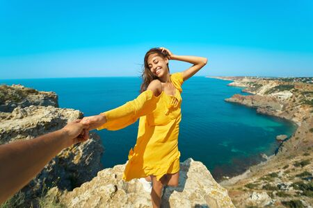 Portrait of happy carefree woman holding hand of her boyfriend, standing on cliff with smile and closing eyes in front of amazing seascape, bright yellow dress and hair blowing in the wind. Follow me, travel, vacation concept.
