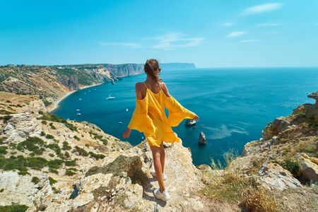Rear view of taned traveler woman standing on cliff edge in front of amazing seascape, bright yellow dress blowing in the wind. Freedom, travel and vacation concept.