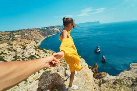 Follow me, first person view of taned traveler woman standing on cliff edge in front of amazing seascape, woman holding hand of her boyfriend, bright yellow dress blowing in the wind. Follow me, active and travel lifestyle concept