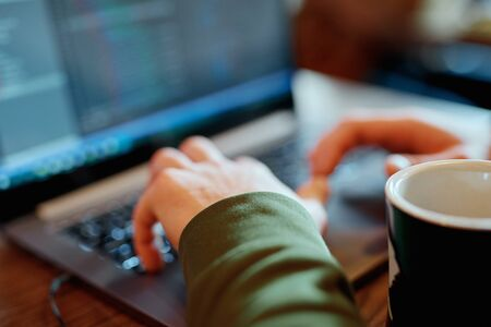 closeup mans hands programmer freelancer sitting in cafe working using laptop, man types, codes, Writes Emails, Surfs the Internet, Designs Software. cup of coffee on table Zdjęcie Seryjne