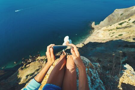 first person view of female tourist sitting on cliff edge with beautiful sea view and taking picture of legs above the water on smartphone camera. Freedom, travel and vacation concept. Zdjęcie Seryjne