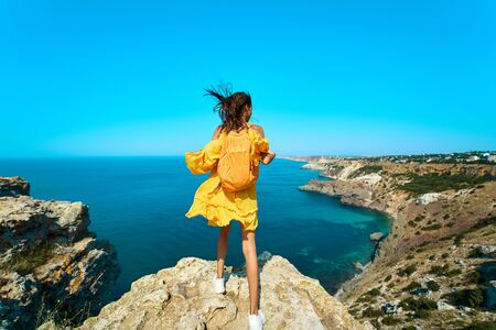 Rear view of traveler woman standing on top rock beach with backpack in front of amazing seascape, bright yellow dress and hair blowing in the wind. Freedom, travel and vacation concept.