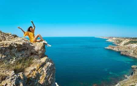 side view of traveler woman in bright yellow dress sitting on cliff edge with raised hands in front of amazing seascape, and enjoying wonderful nature. amazing panorama of seashore landscape. Freedom, travel and vacation concept.