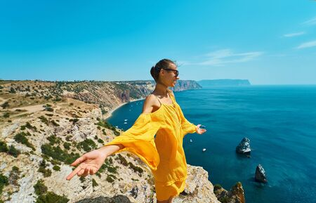 Happy attractive taned woman posing with arms spread open on cliff edge with beautiful sea view. Carefree female in bright yellow dress blowing in the wind. Freedom, travel and vacation concept. Zdjęcie Seryjne