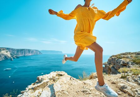 Close-up womans tanned legs making dinamic move, running on cliff against amazing seascape. Bright yellow dress blowing in wind. Active and travel lifestyle concept. Zdjęcie Seryjne