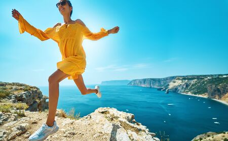 Happy tanned woman making dinamic move, running on on cliff against amazing seascape, seashore. Smiling girl in sunglasses and bright yellow dress blowing in wind. Active and travel lifestyle concept.