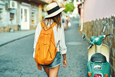 Rear view tourist girl walking on old city street, summer adventure vacation in Europe. Attractive woman in straw hat, white shirt and orange backpack sightseeing town.