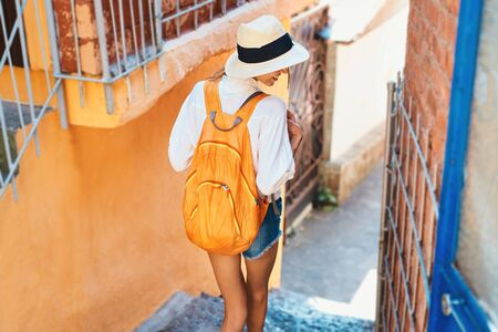 rear view tourist woman in straw hat, white shirt and orange backpack walking narrow street with bright orange walls. Summer vacation in Europe, Mediterranean. Tourism and travel concept.