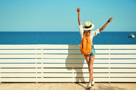 Rear view woman tourist in straw hat, white shirt and orange backpack enjoying sea view at sunny day. Vacation in Mediterranean. Tourism and travel concept.