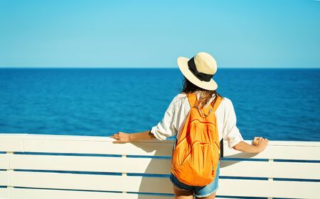 Back view woman tourist in straw hat, white shirt and orange backpack enjoying sea view at sunny day. Vacation in Mediterranean. Tourism and travel concept.
