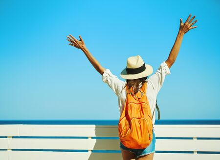 Rear view woman tourist in straw hat, white shirt and orange backpack with raised hands against blue sky at sunny day. Vacation in Mediterranean. Tourism and travel concept. Zdjęcie Seryjne