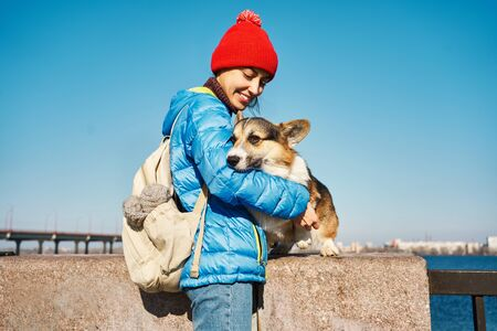 Smiling girl taking free time with her dog outdoors, dog walking. Loving young woman stroking and embracing cute Corgi dog at sunny spring day 版權商用圖片