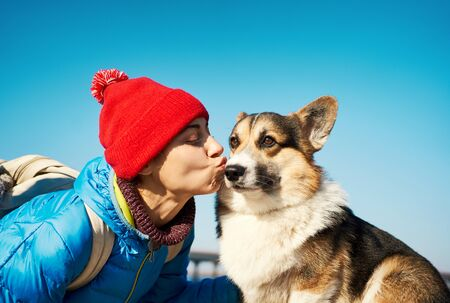 Joyful girl taking free time with her dog outdoors, dog walking. portrait young woman in red hat kissing cute Corgi dog at sunny spring day.