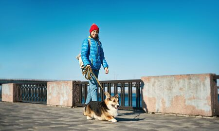 Young woman in blue jacket and red hat walking with cute dog Welsh Corgi at sunny day wiht blue sky. Owner female spending time with lovely pet outdoors.