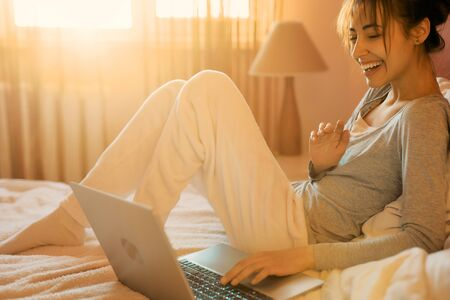 Joyful woman laughting and talking on video call on laptop computer in bed at home, sunlight in bedroom. Positive girl chatting with friends in social networks on laptop device using wireless internet