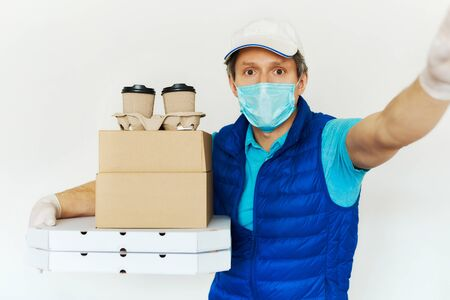 Delivery during quarantine. Courier in uniform face mask gloves carrying many cardboard boxes and packs on doorstep, point of view, first person view. Food delivery service, takeout food concept
