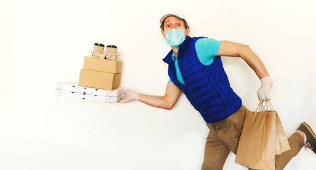 funny delivery man in uniform face mask gloves carrying many cardboard boxes, running and hurrying to deliver takeout food. Food delivery service or shopping order online.