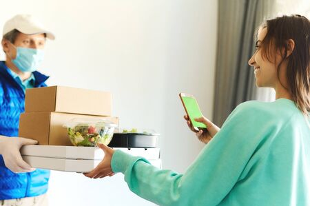 woman receiving packages from delivery man. Courier in uniform face mask gloves holding paper boxes for take out food and bags. Delivery food service at home, shopping order online from smartphone