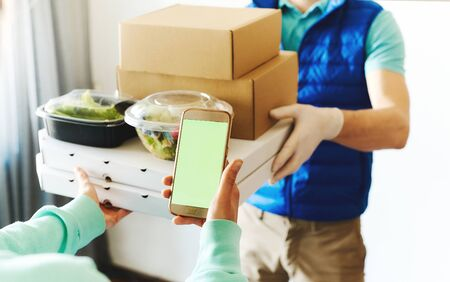 POV of woman using smarthone for ordering online, receiving takeout food from delivery man. Courier holding paper boxes and containers. Delivery food service during quarantine, shopping order online
