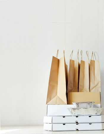 Takeaway paper bags and carton boxes on table in white bright room. Takeout meal, delivery to home, food delivery, online shopping concept