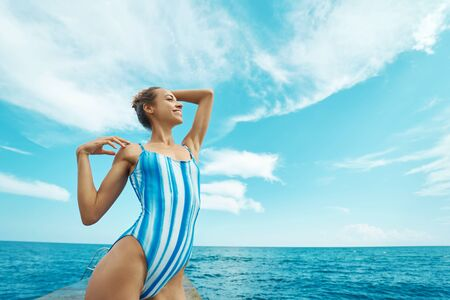 slender happy woman in swimsuit posing and sunbathing against sea ocean view and blue sky. concept summer sea vacation, travel and freedom Imagens