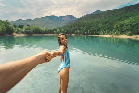 POV and Follow me. Beautiful suntanned smiling woman holding someone hand. Traveler girl enjoying beautiful nature, clear blue lake against mountains. people in nature and travel concept. Imagens