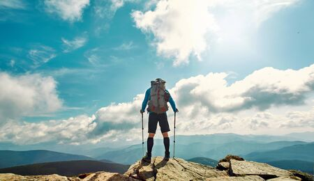 Rear view man traveler hiking stand on top of mountain against beautiful cloudy sky, enjoying nature view, solo traveling. Outdoor adventure, wild journey, people in nature