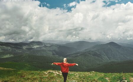 Rear view woman hiker standing on top mountain with open arms. Feeling freedom and harmony. Woman enjoying beautiful nature view, inspiring landscape. Outdoor adventure, wild journey, people in nature