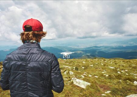 Rear view man controling quadcopter drone with digital camera outdoors. Drone flying over moutains landscape, takes pictures of beautiful scenery of wild nature