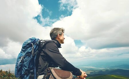 man traveler hiker with big backpack relaxing and enjoying view of beautiful cloudy sky in mountains, amazing scenery wild nature. Outdoor adventure, people in nature, solo traveling.