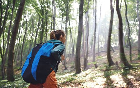 back view woman traveler with big backpack hiking walking on rocky trail throught forest, enjoying scenery of nature, sun rays shine through trees. Outdoor adventure, people in nature, solo traveling.