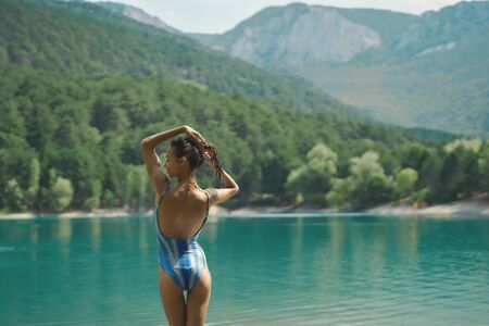 Rear view traveler woman in swimsuit posing on background of mountain lake and mountains in the background, aqua menthe colored water. inspiring landscape and beautiful scenery of nature. Imagens